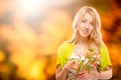 Beautiful young woman over autumn background. Beautiful young woman holding flowers over autumn background Stock Photography