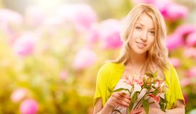 Beautiful young woman over autumn background. Beautiful young woman holding flowers over autumn background Royalty Free Stock Photography
