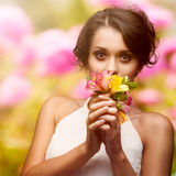 Beautiful young woman over autumn background. Beautiful young woman holding flowers over autumn background Stock Images