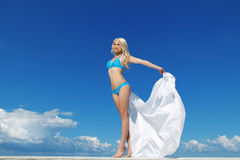 Beautiful young woman over the blue sky Royalty Free Stock Images
