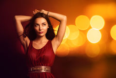 Beautiful Young Woman over Bright Night Lights. Portrait of a Beautiful Young Woman in Fashionable Red Dress over Bright Night Lights. Nightlife Party Concept Stock Photography