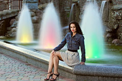 Beautiful young woman over the fountain. At the evening Royalty Free Stock Photo