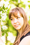 Beautiful young woman over white blossom tree, outdoors portrait.  Royalty Free Stock Images