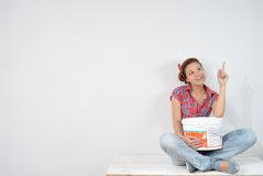 Beautiful young woman with paint bucket thinks over idea of repair Royalty Free Stock Images