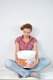 Beautiful young woman with paint bucket thinks over idea of repair Royalty Free Stock Photography