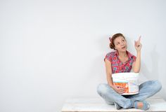 Beautiful young woman with paint bucket thinks over idea of repair Stock Photos