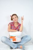 Beautiful young woman with paint bucket thinks over idea of repair Stock Photo