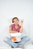 Beautiful young woman with paint bucket thinks over idea of repair Stock Image