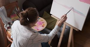 Woman painting on canvas. Beautiful young woman painting on canvas at easel stock footage