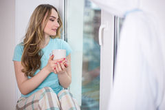 Beautiful young woman in pajamas sitting by the window with cup Royalty Free Stock Photos