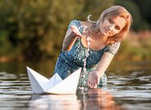 Beautiful young  woman with a paper boat by the lake in summertime Royalty Free Stock Images