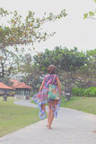 Beautiful young woman in pareo and swimsuit walking in the becah park with bag on sunny summer day. Tropical island Bali Royalty Free Stock Image