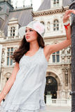 Beautiful Young Woman in Paris. Beautiful young woman in a fashion pose in a plaza in Paris, France with typical French architecture in the background royalty free stock photo