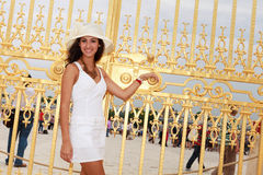Beautiful young woman in Paris. Beautiful young woman at the golden gates of Versailles palace in Paris, France Royalty Free Stock Photos