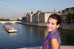 Beautiful young woman on a Paris Bridge. Beautiful young woman posing on a bridge over the river Seine in Paris with a water boat taxi passing by stock photos