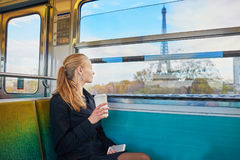 Beautiful young woman in Parisian subway. Beautiful young woman travelling in a train of Parisian underground and drinking coffee. Eiffel tower is behind the Stock Photo