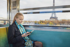 Beautiful young woman in Parisian subway. Beautiful young woman travelling in a train of Parisian underground and reading a book. Eiffel tower is behind the Stock Photo