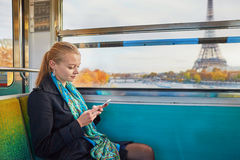 Beautiful young woman in Parisian subway. Beautiful young woman travelling in a train of Parisian underground and using her mobile phone. Eiffel tower is behind Stock Photography