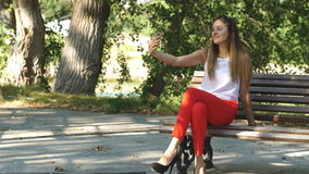 Beautiful young woman on a Park bench taking a selfie. Beautiful young womanin red pants on a Park bench taking a selfie stock footage