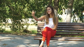 Beautiful young woman on a Park bench taking a selfie. Beautiful young womanin red pants on a Park bench taking a selfie stock video footage