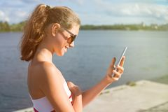Beautiful young woman in the park using cellphone. In sun glasses, against the background of water, sunset royalty free stock photo