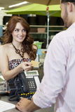 Beautiful young woman paying through credit card in store Stock Image