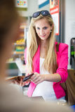 Beautiful young woman paying for her groceries at the counter Stock Photos
