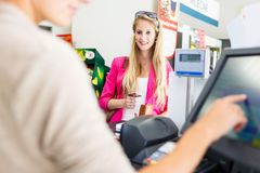 Beautiful young woman paying for her groceries at the counter Royalty Free Stock Photos