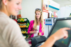 Beautiful young woman paying for her groceries Stock Images