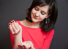 Beautiful young woman with a pearl necklace. Beautiful young woman holding a pearl necklace Royalty Free Stock Photo