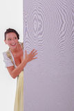 Beautiful young woman peeking out behind wall of office or school Royalty Free Stock Image