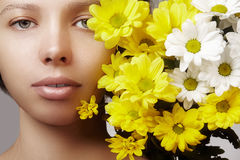 Beautiful young woman with perfect clean shiny skin, natural fashion makeup with spring flowers. Close-up woman, fresh spa look Royalty Free Stock Photo