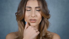 Beautiful young woman with perfect face isolated on grey background. stock video footage