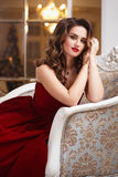 Beautiful young woman with perfect make up and hair style in gorgeous red evening dress in expensive luxury interior Royalty Free Stock Photo
