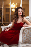 Beautiful young woman with perfect make up and hair style in gorgeous red evening dress in expensive luxury interior Stock Images
