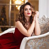 Beautiful young woman with perfect make up and hair style in gorgeous red evening dress in expensive luxury interior Stock Photos