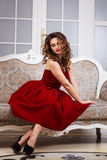 Beautiful young woman with perfect make up and hair style in gorgeous red evening dress in expensive luxury interior Stock Image