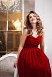 Beautiful young woman with perfect make up and hair style in gorgeous red evening dress in expensive luxury interior Royalty Free Stock Images