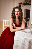 Beautiful young woman with perfect make up and hair style in gorgeous red evening dress in expensive luxury interior Royalty Free Stock Image