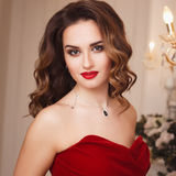 Beautiful young woman with perfect make up and hair style in gorgeous red evening dress in expensive luxury interior Stock Photography