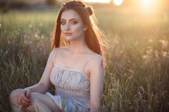 Beautiful young woman with perfect make up and long plaited hair sitting in the field at sunset. Wearing cotton ethnic summer dress. Backlight. Text space stock image