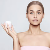 Beautiful young woman. With perfect skin, blond hair and cream in hand Royalty Free Stock Photos