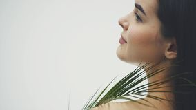 A beautiful young woman with perfect skin and natural makeup poses in front of the camera. Tropical green leaves of the. Fern background. Young models with stock video footage