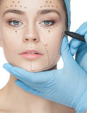 Beautiful young woman with perforation lines on her face before plastic surgery operation. Beautician touching woman face and drawing lines Stock Photography