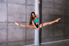 Beautiful young woman performing pole dance elements Royalty Free Stock Image