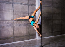 Beautiful young woman performing pole dance elements Stock Images