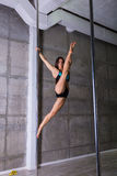 Beautiful young woman performing pole dance elements Royalty Free Stock Photo