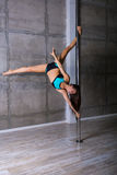 Beautiful young woman performing pole dance elements Royalty Free Stock Photography