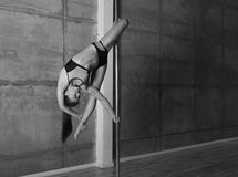 Beautiful young woman performing pole dance elements Royalty Free Stock Photos
