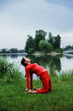 Beautiful young woman performing yoga exercises. On the lake. Ushtrasana Royalty Free Stock Photos